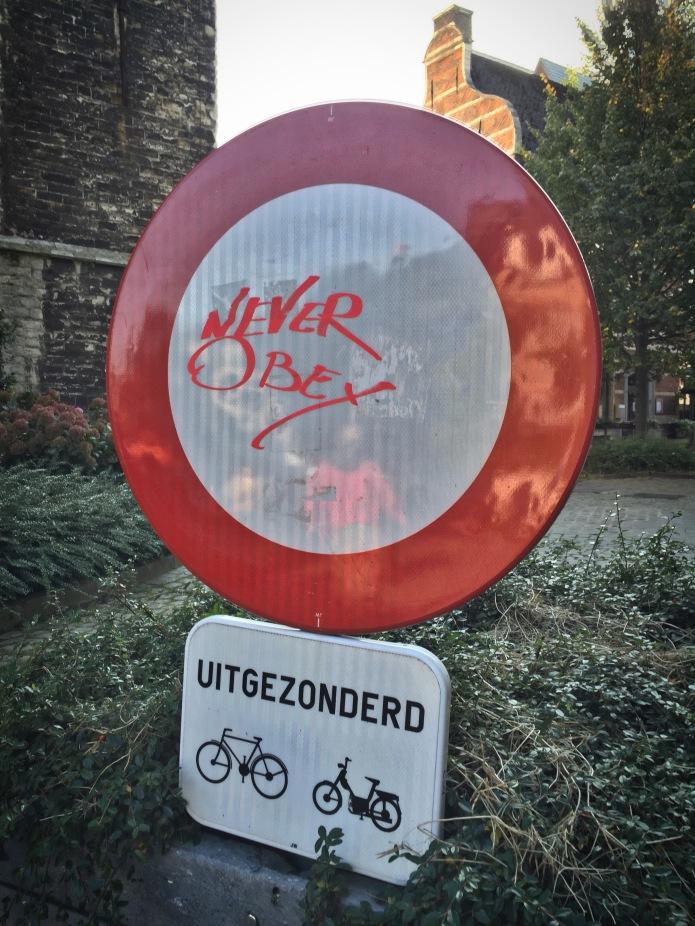Teken aan de wand #65 Never Obey. Leuven, Halfmaartstraat, 11 oktober 2015, Foto Hendrik Elie Vanden Abeele. Te Voet in de Stad