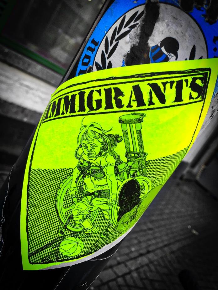 Plakkatief #19 Immigrants. Leuven, Kapucijnenvoer, 29 november 2015, Foto Hendrik Elie Vanden Abeele. Te Voet in de Stad